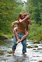 Young woman covering eyes of young man giving piggy back ride in stream