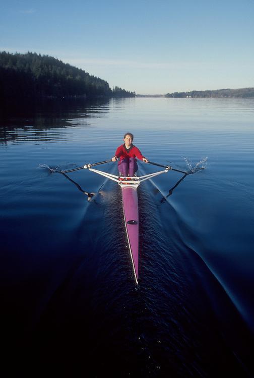 Rowing, Woman rowing single racing shell at full pressure, Lake Whatcom, Bellingham, Washington,