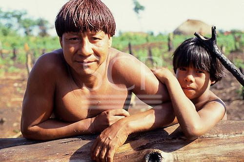 Xingu, Brazil. Pavuru; Ikpeng man with red Urucum dyed hair and his son.