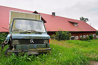 A rusty old Mercedes truck lorry in a field. Traditional style Swedish wooden painted house. Barn Smaland region. Sweden, Europe.
