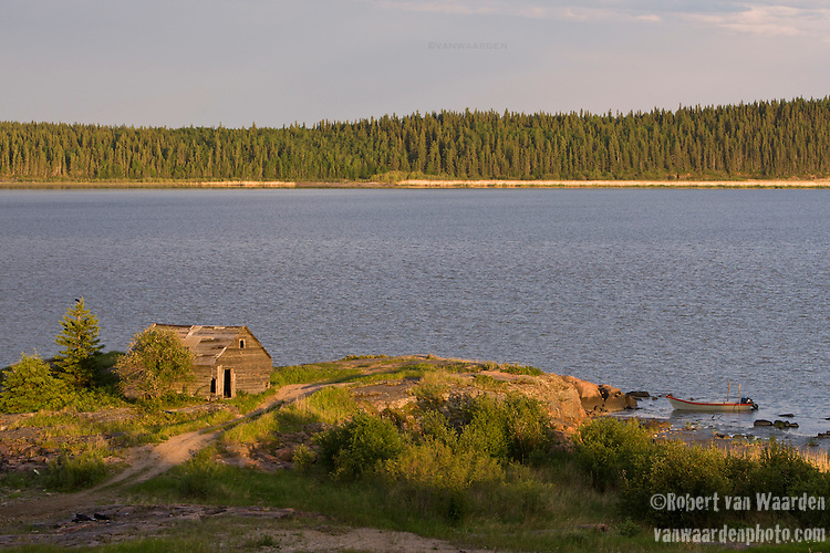A cabin and boat sit on a point near Fort Chipewyan on Lake Athabaska.