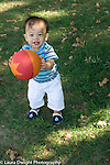 12 month old toddler boy outside walking holding ball happy vertical
