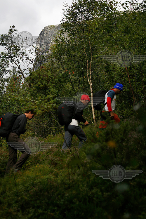 Competitors walk through a forest on their way to the mountain top. World BASE Race is held in Innfjorden, Norway, where BASE jumpers in wingsuits compete in flying down the mountain. The winner is called the World's Fastest Flying Human Being..©Fredrik Naumann/Felix Features.