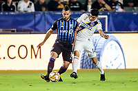CARSON, CA - SEPTEMBER 21: Joe Corona #14 of the Los Angeles Galaxy slides battles Saphir Taïder #8 of the Montreal Impact for a loose ball during a game between Montreal Impact and Los Angeles Galaxy at Dignity Health Sports Park on September 21, 2019 in Carson, California.