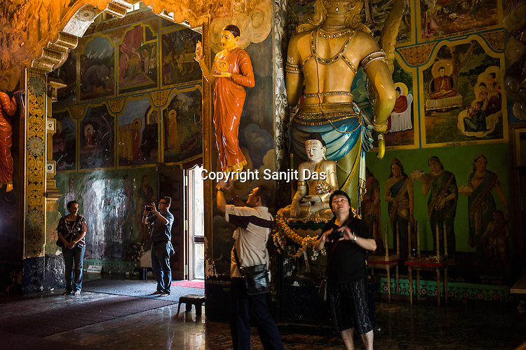 Buddhist Sri Lankans visit the local Buddhist temple in Colombo, Sri Lanka.  Photo: Sanjit Das/Panos