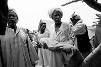 Farchana, Tchad, June 5, 2004.A sheikh takes the tiny body of Hafiz Malik Yaya, 9 months old, dead of severe malnutrition for burial. More than 13 thousand Sudanese refugees from Darfur stay in this camp in very harsh conditions.