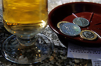 Glass of beer being paid for at a cafe, Paris, France.