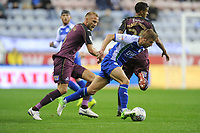 Mike van der Hoorn of Swansea City vies for possession with Michael Jacobs of Wigan Athletic during the Sky Bet Championship match between Wigan Athletic and Swansea City at the DW Stadium in Wigan, England, UK. Friday 02 October 2018