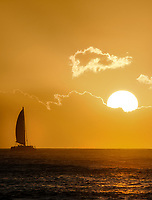Sailboat at sunset off Kauai coast. Hawaii