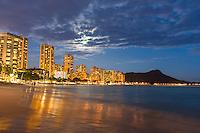 A couple in the distance walk Waikiki Beach under a full moon on O'ahu.