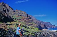 A camper has a cup of coffee on rocks near Kalalau Beach on the Na Pali Coast