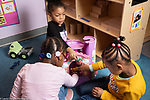 Education preschool 4 year olds three girls playing with plastic castle and small dolls
