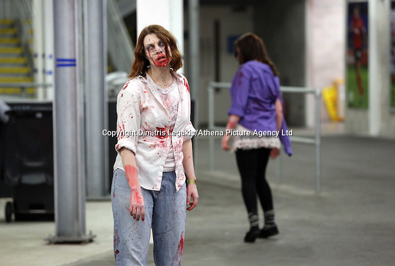 Pictured: Zombies at the Cardiff City football stadium. Saturday 29 March 2014<br /> Re: Cardiff thrill-seekers were chased around the city last night by a horde of terrifying zombies as part of virtual apocalypse game 2.8 Hours Later.<br /> Starting in Grangetown, groups of zombie-enthusiasts walked, jogged, hid and run around a quarantined area of the city, which included Cardiff City Stadium and Ninian Park Primary School, to escape a deadly mass of infected undead.<br /> But it wasn't just zombies threatening to disturb the peace of the city – aggressive police and surveillance squads forcing people to stand up against walls and avoid their harmless friends for fear of spreading infection wreaked havoc in the quarantine.
