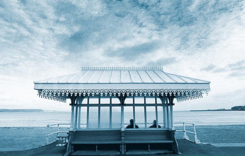 Two men sat in Victorian shelter looking out to sea,  Weymouth, Dorset, England