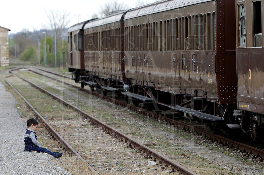 Un bambino seduto sul marciapiede della stazione di Torrenieri-Montalcino, davanti a un treno d'epoca degli anni Venti, in occasione della presentazione degli itinerari storici proposti dal Ministero dei Beni Culturali e del Turismo e dalla Fondazione FS Italiane, lungo il tracciato dell'antica ferrovia della Val d'Orcia, 11 aprile 2015.<br /> A child sits in front of a vintage train of the twenties traveling on the occasion of the presentation of the historical tours proposed by the Italian Culture and Tourism Minister and Fondazione FS Italiane (Italian Railways Foundation), at Torrenieri-Montalcino's railway station, along the Val d'Orcia, Tuscany, 11 April 2015.<br /> UPDATE IMAGES PRESS/Riccardo De Luca