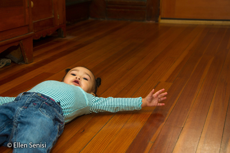 MR / Schenectady, NY. Toddler (1 year and 2 months old, African-American and Caucasian) in early walking stage lying on her back after falling down. MR: Dal4. ID: AM-HD. © Ellen B. Senisi