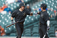 Walker Grisanti (left) of the Vanderbilt Commodores slaps hands with teammate Ethan Paul (right) after scoring a run in the 10th inning against the Sam Houston State Bearkats in game one of the 2018 Shriners Hospitals for Children College Classic at Minute Maid Park on March 2, 2018 in Houston, Texas. The Bearkats walked-off the Commodores 7-6 in 10 innings.   (Brian Westerholt/Four Seam Images)