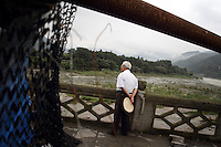"A man looks out onto the Dujiangyan Irrigation System. The system is regarded as an ""ancient Chinese engineering marvel."" By naturally channeling water from the Min River during times of flood, the irrigation system served to protect the local area from flooding and provide water to the Chengdu basin. Sichuan Province. 2010"