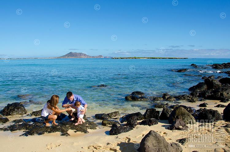 Mom and dad helping their infant son walk along black rocks on Kailua beach, Windward O'ahu