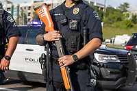 "AUSTIN, TEXAS - MAY 30, Austin Police officers standing on IH-35 holds a less lethal shotgun during a Black Lives Matter protest rally on May 30, 2020 in Austin, Texas. These weapons occasionally cause serious injuries or death; the term ""less-lethal"" has been preferred by some organizations as it describes the risks of death more accurately than the term ""non-lethal"", which some have argued is a misnomer.<br />