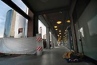 Milano / Italia 2013.Un homeless dorme per strada nei pressi della stazione ferroviaria di Pta Garibaldi. I senza fissa dimora a  Milano son 13.000 e la loro condizione contrasta con l'immagine dei moderni grattacieli recentemente costruiti in occasione della prossima EXPO 2015..A homeless sleeping on the streets near the train station Pta Garibaldi. The homeless in Milan are 13,000 and their condition contrasts with the image of modern skyscrapers recently built at the next EXPO 2015.Photo Livio Senigalliesi