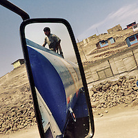 A Peruvian water distribution worker climbs up the water truck on the dusty hillsides of Pachacútec, a desert shantytown in Lima, Peru, 19 January 2015.