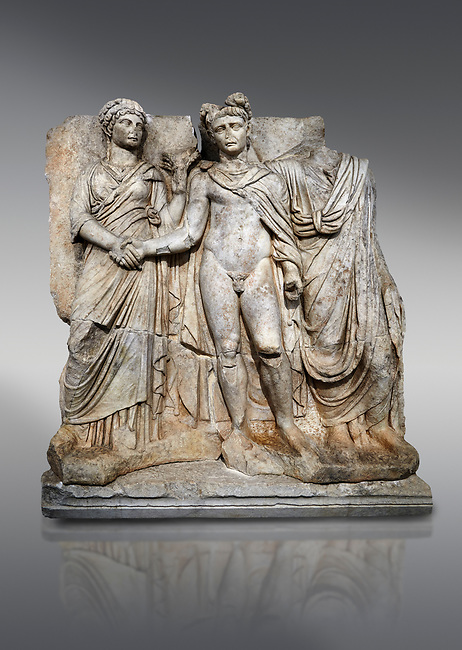 """Roman Sebasteion releif sculpture of emperor Claudius and Agrippina, Aphrodisias Museum, Aphrodisias, Turkey. <br /> <br /> Claudius in heroic nudity and military cloak shakes hands with his wife Agrippina and is crowned by the Roman people or the Senate wearing a toga. The subject is imperial concord with the traditional Roman state. Agrippina holds ears of wheat: like Demeter goddess of fertility. The emperor is crowned with an oak wreath, the Corona civica or """"citizen crow"""", awarded to Roman leaders for saving citizens lives: the emperor id therefore represented as saviour of the people."""