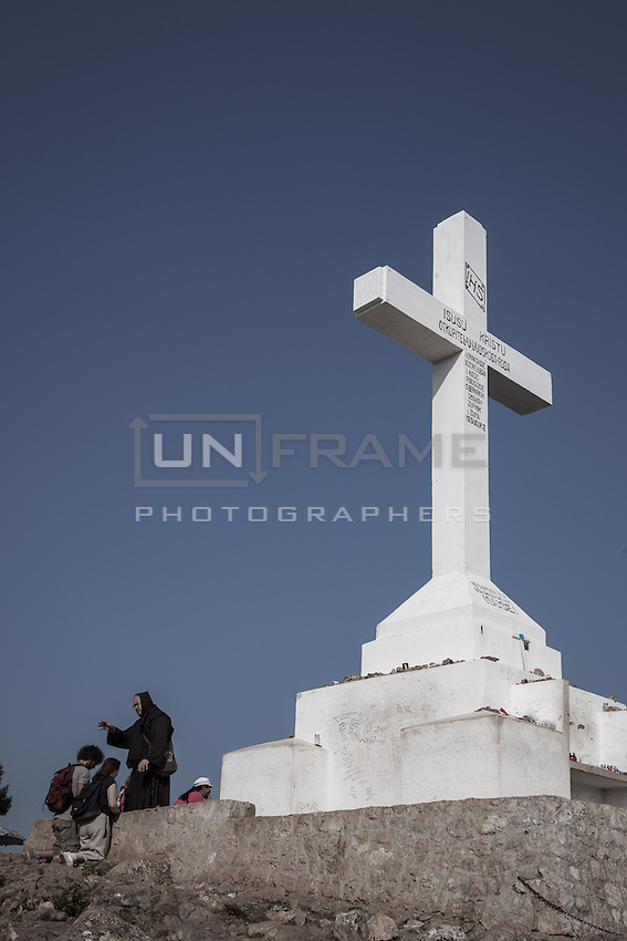 A friar blessing two pilgrims near the concrete cross on top of the Mt. Krizevac.<br /> Medjugorje, Bosnia and Herzegovina. July 2012