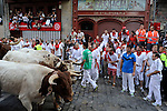 Participants watch the leading steers of Torrestrella during the fifth bull run of the San Fermin Festival in Pamplona, northern Spain on July 11, 2013. © Pedro ARMESTRE