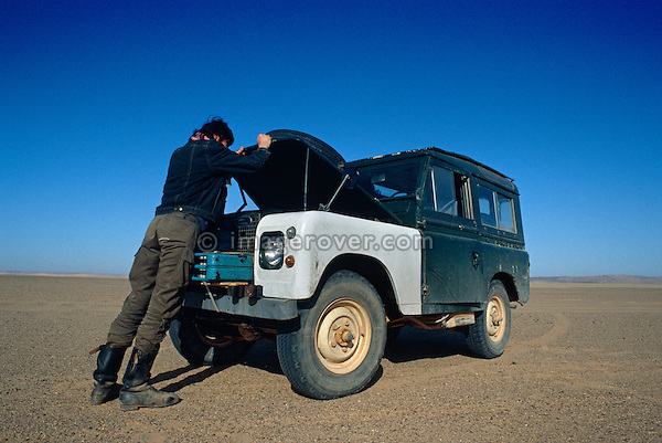Africa, Algeria, Sahara Desert. Traveller, undertaking a sahara trip with his Series 2a Land Rovers 88, checking his vehicle during a day longs off road drive. --- No releases available. Automotive trademarks are the property of the trademark holder, authorization may be needed for some uses.