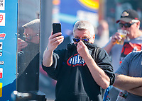 Feb 7, 2020; Pomona, CA, USA; An NHRA fan reacts by covering his face from the nitromethane fumes as a car warms up in the pits during qualifying for the Winternationals at Auto Club Raceway at Pomona. Mandatory Credit: Mark J. Rebilas-USA TODAY Sports