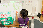 Education preschool 3 year olds girl writing or drawing on daily schedule dry erase board using left hand