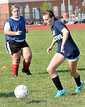 TERRYVILLE, CT - 31 August 2012-083112EC03--    Cassie Powell dribbles the ball during a drill Friday afternoon in Terryville.  Behind her is Emilee Carusillo.  The Thomaston and Terryville girls soccer teams have combined for the fall season.  Erin Covey Republican American.