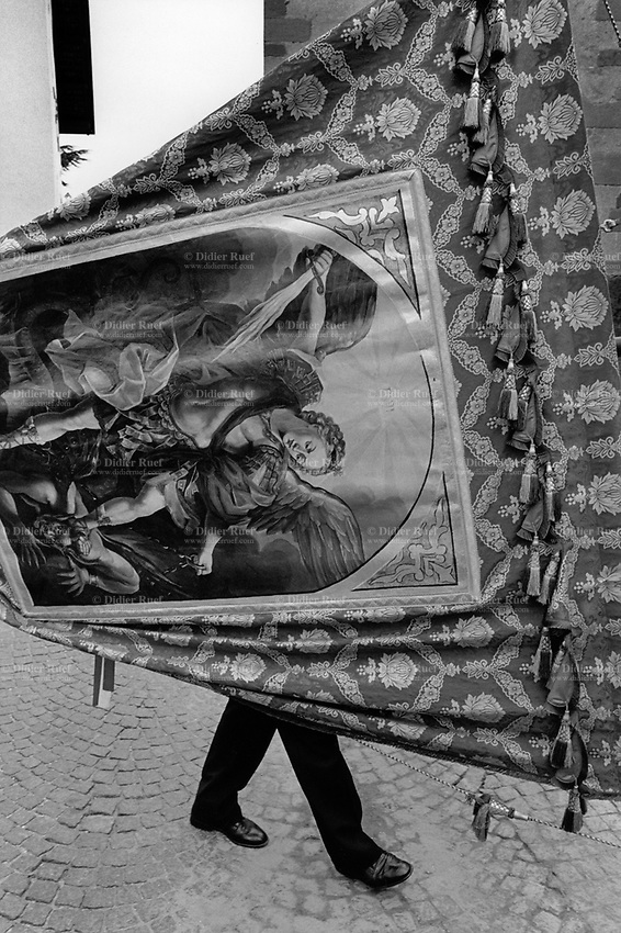 """Italy. South Tyrol. Tisens. Religious procession on August 15 for the Assumption. A man carries a painting from the New Testament depicting Michael leading God's armies against Satan's forces in the Book of Revelation, where during the war in heaven he defeats Satan. Roman Catholics refer to him as """"Saint Michael the Archangel"""". The Assumption of the Virgin Mary into Heaven, often shortened to the Assumption, is also known as the Falling Asleep of the Blessed Virgin Mary, According to the beliefs of the Catholic Church was the bodily taking up of the Virgin Mary into Heaven at the end of her earthly life. The Assumption is a major feast day, commonly celebrated on August 15th. The feast is marked as a Holy Day of Obligation in the Roman Catholic Church. South Tyrol (German: Südtirol; Italian: Sudtirolo, also known by its alternative Italian name Alto Adige) is an autonomous province in northern Italy. 15.08.1999 © 1999 Didier Ruef"""