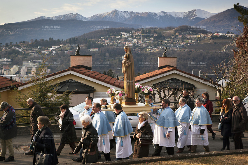 """Switzerland. Canton Ticino. Pregassona. Religious procession. Four men carry a wooden sculpture of The Virgin Mary holding the baby Jesus during the """"Festa patronale La Candelora"""". Mary was a 1st-century BC Galilean Jewish woman of Nazareth, and the mother of Jesus, according to the New Testament. Christians believe that she conceived her son while a virgin by the Holy Spirit. The Gospel of Luke begins its account of Mary's life with the Annunciation, when the angel Gabriel appeared to Mary and announced her divine selection to be the mother of Jesus. The Catholic Church holds distinctive Marian dogmas, namely her status as the Mother of God, her Immaculate Conception, her perpetual virginity, and her Assumption into heaven. Pregassona is quarter of the city of Lugano and a former municipality in the district of Lugano. 4.02.2018 © 2018 Didier Ruef<br /> <br /> <br /> ."""