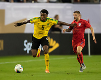 NASHVILLE, TN - JULY 4: Elvis Powell #5 attacks with Paul Arriola #7 in pursuit during a game between Jamaica and USMNT at Nissan Stadium on July 4, 2019 in Nashville, Tennessee.