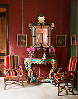 An 18th century Venetian mirror hangs above a painted console in a hallway which is furnished with Regency armchairs