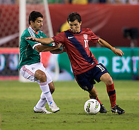 Jose Torres (11) of the USMNT fights his way past Antonio Naelson (17) of Mexico during the game at Lincoln Financial Field in Philadelphia, PA. The USMNT tied Mexico, 1-1.