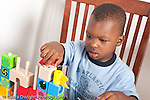 3 year old boy at home playing with blocks and spindle toy horizontal