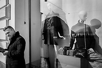 Switzerland. Canton Ticino. Lugano. A man checks his mobile phone while standing in front of fashion boutique. 8.02.2020 © 2020 Didier Ruef