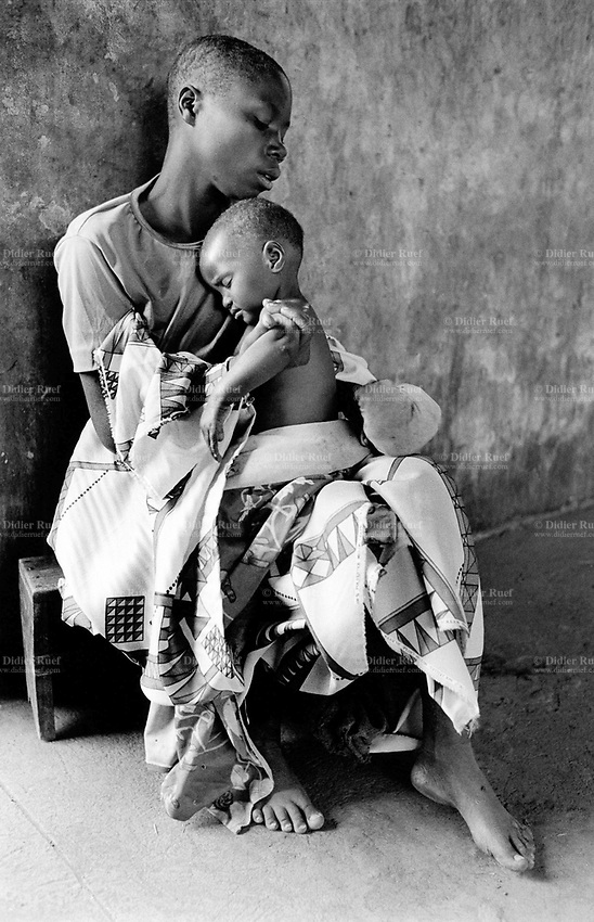 Burundi. Karuzi Province. Rabiro. Bare feet mother holding in her arms her child who is asleep. © 2000 Didier Ruef