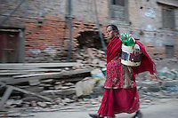 A woman runs to collect drinking water in Bhaktapur, near Kathmandu, Nepal. May 04, 2015