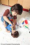 Education preschool 3-4 year olds pretend play girl using medical kit on doll vertical