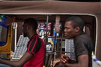 """Nigeria. Enugu State. Enugu. Town center. An auto rickshaw used by a """"Keke"""" driver for transporting Igbo people around town. The  tricycle better known in Nigeria as the Keke NAPEP is gaining the dominance on Nigerian roads sweeping every street of cities and villages. The auto rickshaw is a common form of urban transport, both as a vehicle for hire and for private use. In the background, a shop sells solar panels and various electronic items. Enugu is the capital of Enugu State, located in southeastern Nigeria. 15.07.19 © 2019 Didier Ruef"""
