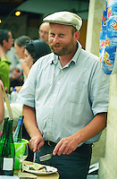 Victor Lebreton from Domaine de Montgilet in Anjou (Loire) drinking his own wine at a wine fair in Paris and eating some cheese for lunch. Wearing a cap and a beard., Maine et Loire France Anjou