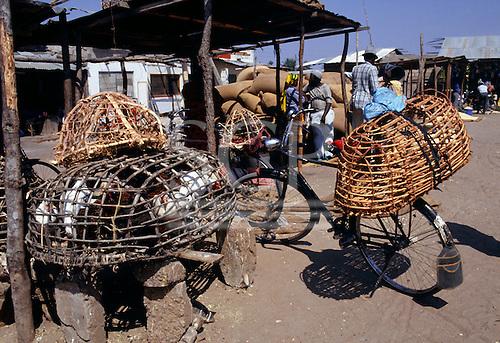 Tabora, Tanzania. Chickens in hand made latticework basket cages; market.
