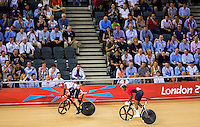 06 AUG 2012 - LONDON, GBR - Jason Kenny (GBR) of Great Britain (left) watches Njisane Nicholas Phillip (TRI) of Trinidad and Tobago during their Individual Sprint semi final first race at the London 2012 Olympic Games track cycling at the Olympic Park Velodrome in Stratford, London, Great Britain (PHOTO (C) 2012 NIGEL FARROW)