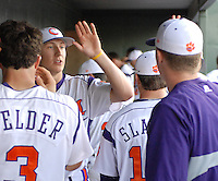 Starting pitcher Daniel Gossett (23) of the Clemson Tigers high-fives his teammates from the dugout in a game against the Elon College Phoenix on March 21, 2012, at Fluor Field at the West End in Greenville, South Carolina. Clemson's 4-2 win was Gossett's first college win and head coach Jack Leggett's 1,200th career win.