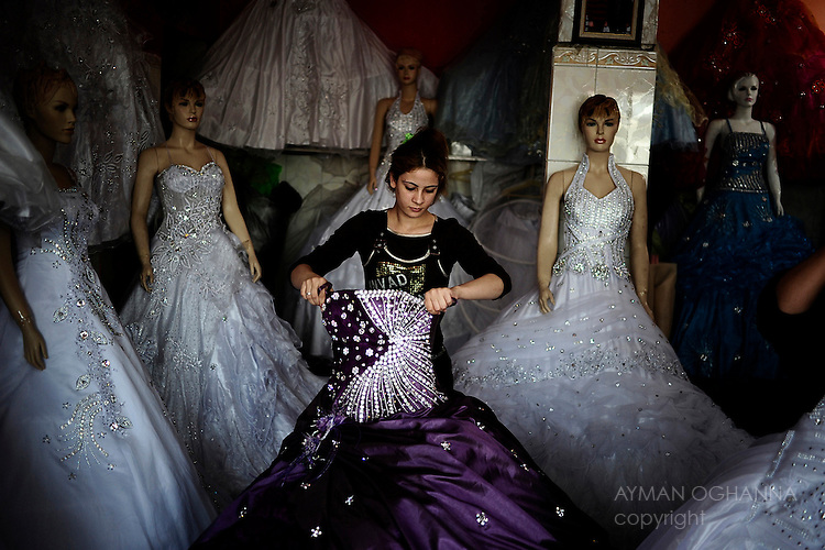An unveiled Nithal Hussein, 19, at  work a store renting  wedding dresses in Baghdad's notorious slum, Sadr City. ..