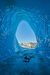 """Pictured: A hiker is dwarfed by the opening of a huge ice cave.   The ice cave in Iceland formed inside of an iceberg which was locked into a frozen lagoon as temperatures dropped to -12 degrees Celsius.<br /> <br /> Professional photographer Mark Andreas Jones captured these shots looking out of two caves in Hoffellsjökull as his friend Oskar Arason walked by.   Mr Jones, 49, from Gosport, Hants, said: """"Up to 90 per cent of the iceberg was submerged so it was impossible to gauge the full size of it, but the smallest of the two caves was easily the size of a four-bedroom house above the water level.   SEE OUR COPY FOR DETAILS<br /> <br /> Please byline: Mark Andreas Jones/Solent News<br /> <br /> © Mark Andreas Jones/Solent News & Photo Agency<br /> UK +44 (0) 2380 458800"""
